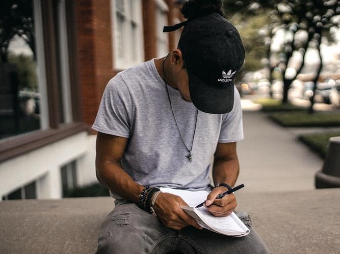 Chico escritor escribiendo la historia de un libro en su cuaderno